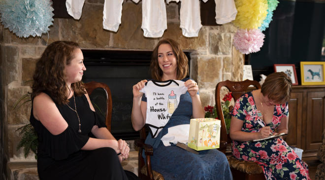 pregnant woman at her baby shower opening gifts