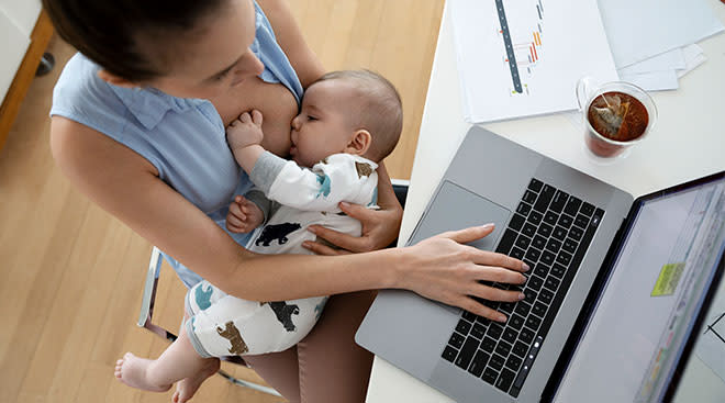 mom working on computer and breastfeeding her baby