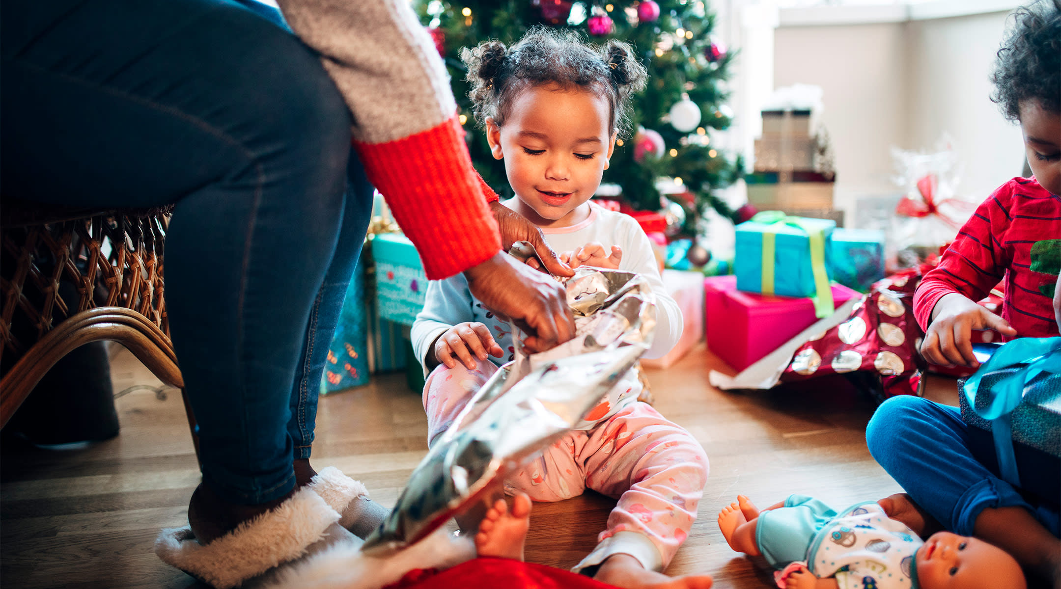 toddler girl opening up her christmas gifts