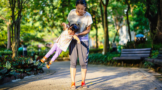 Mom lifting up and playing with her daughter in a tree-lined park.