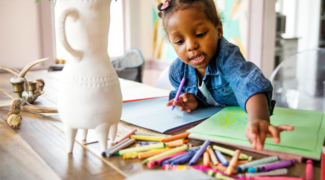toddler girl coloring with crayons at home