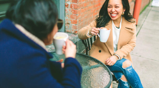 two friends laughing and enjoying coffee