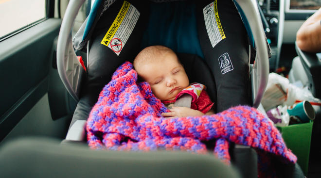 Little baby sleeping in car in forward facing car seat.