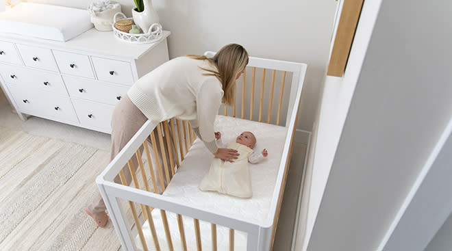 mom placing baby in crib