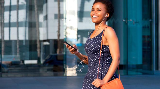 happy woman walking in urban setting