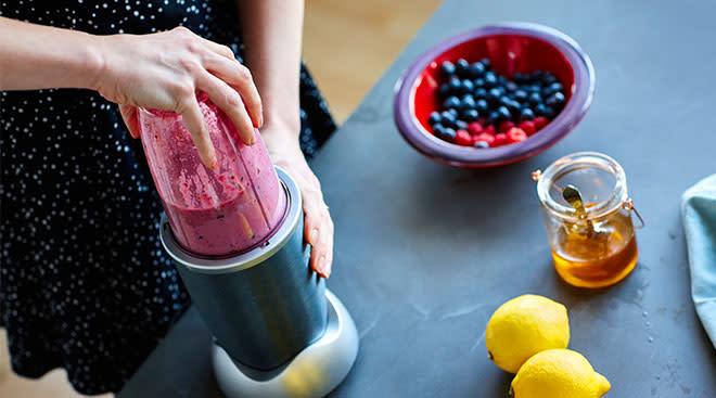 hands using blender to make healthy fruit based baby food