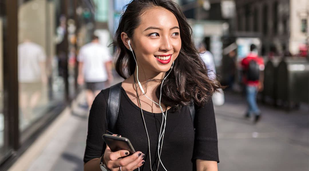 young woman smiling coyly and and walking through city streets