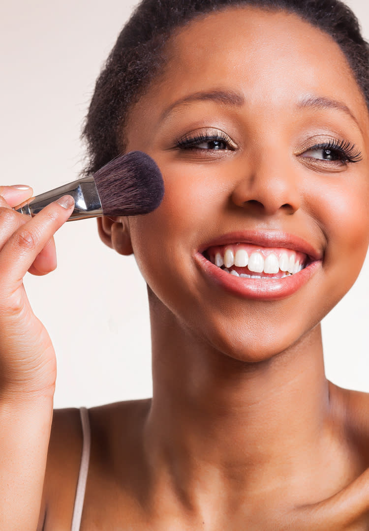Close-up of woman applying powder make-up with brush.