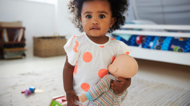 toddler looking at camera and holding doll