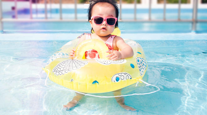 baby wearing a floatie and sunglasses in the swimming pool.