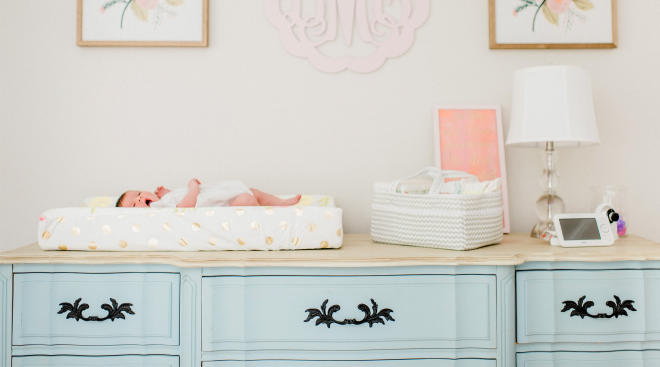 baby laying on changing pad in nursery