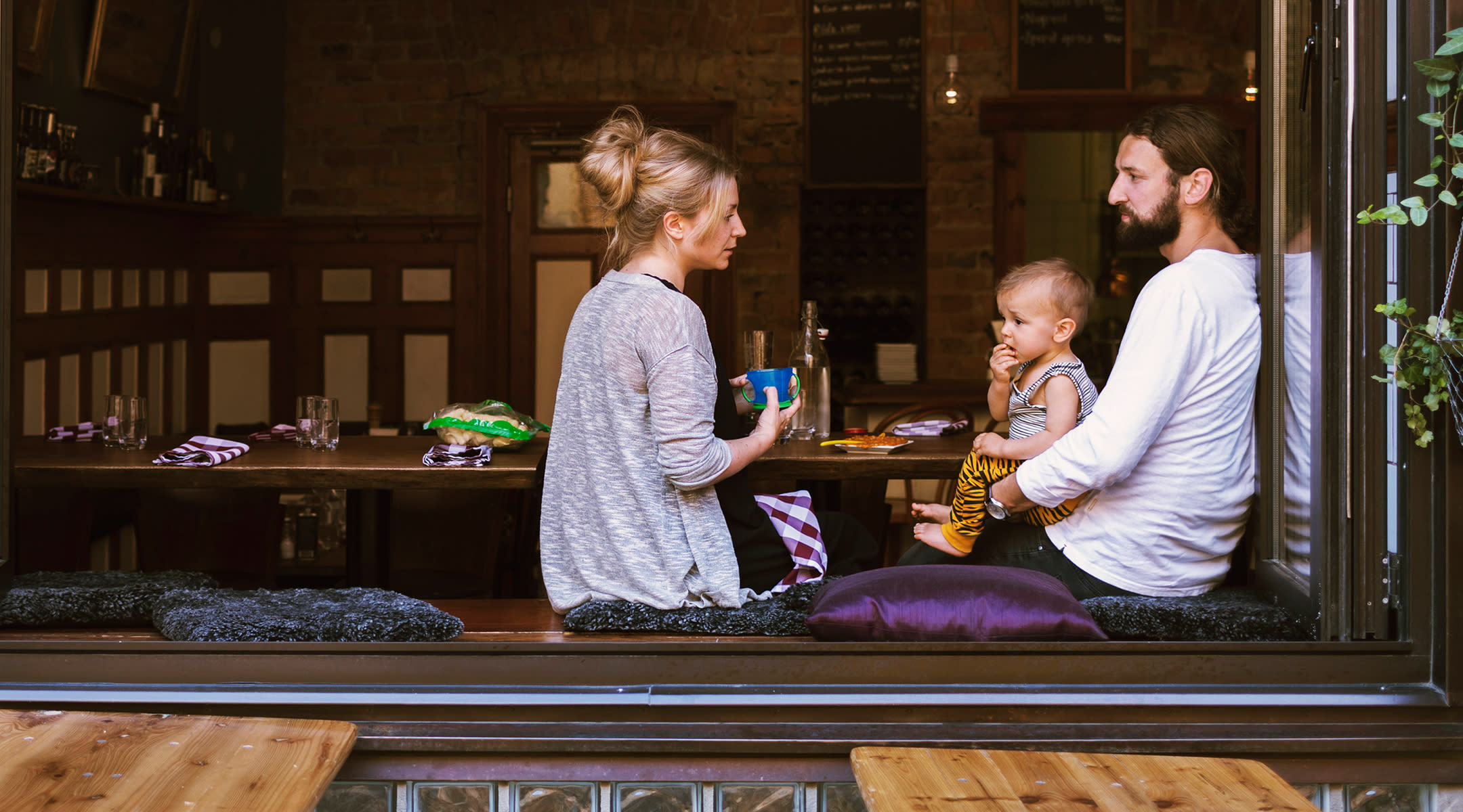Couple eating in open air restaurant with baby