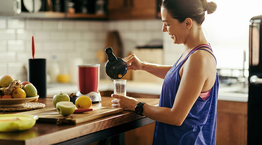 healthy woman making smoothie in kitchen