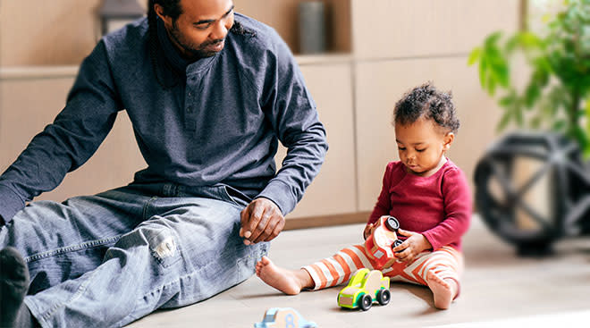 dad playing toy cars with his toddler daughter