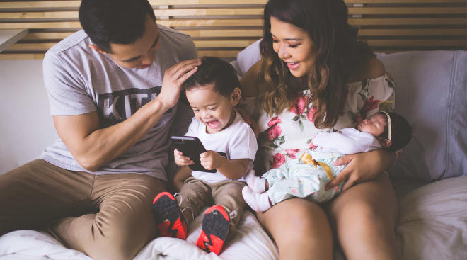 happy family laughing on bed together