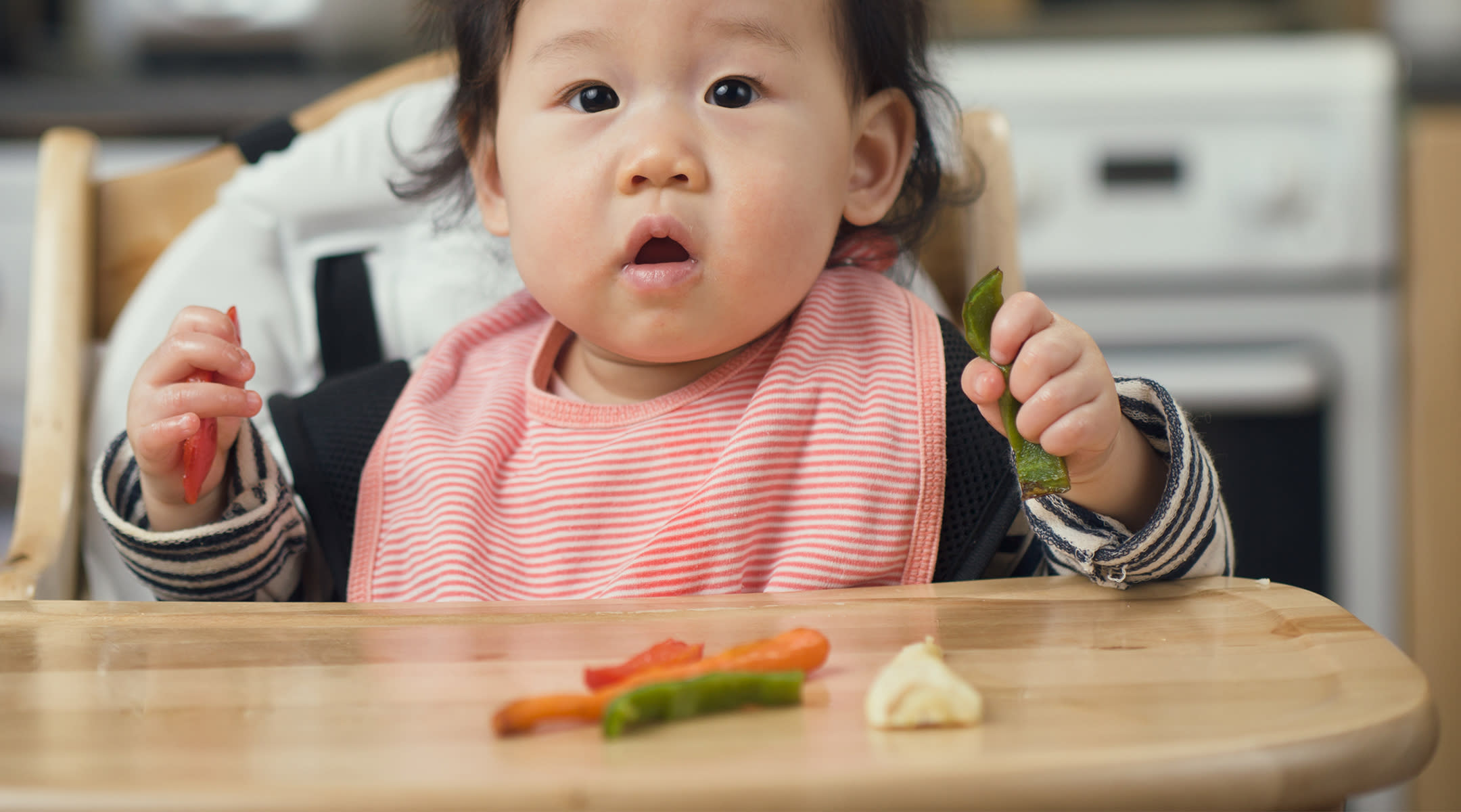 the best time to start allergy prevention for baby in utero says baby playing vegetables in high chair