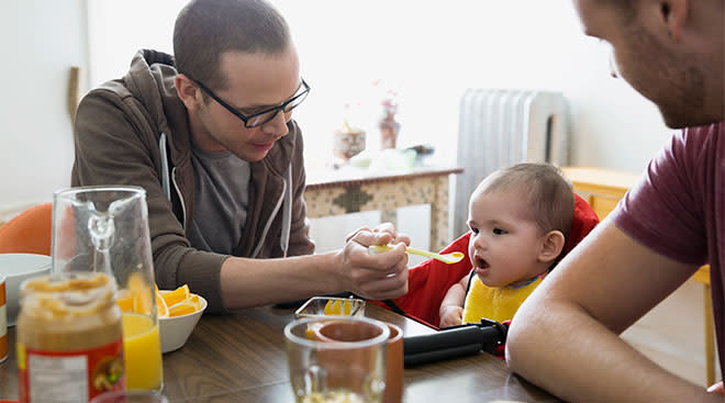 Dads feeding their baby, baby food at kitchen table.