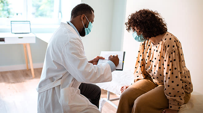 Woman talking to her doctor at the doctor's office.
