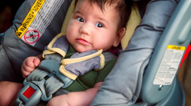 baby sitting in rear facing car seat inside car
