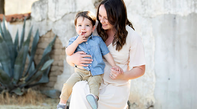 Pregnant mom holds her happy toddler who is dressed up for a special event.