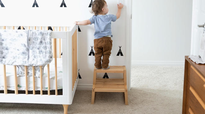 toddler using step stool in his nursery to turn on the light