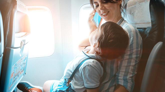 woman flying in airplane with toddler on her lap