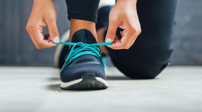 close up of woman tying her running sneakers