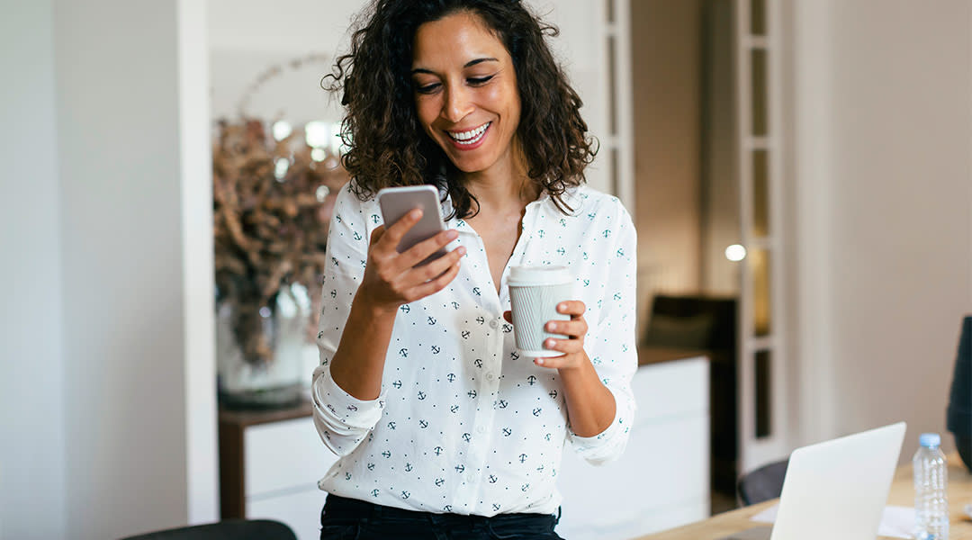 woman laughing and looking at her phone