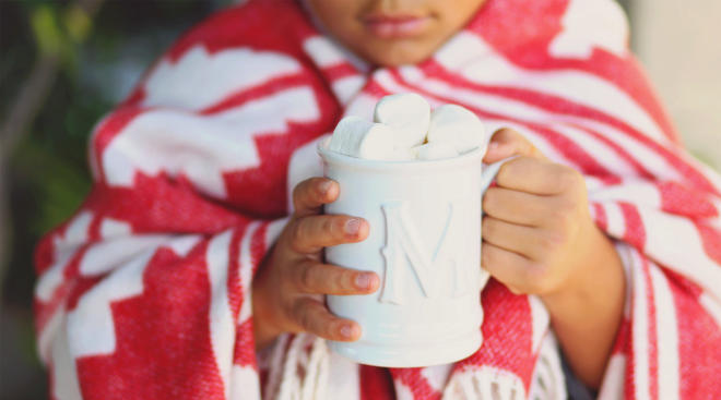 child wrapped in blanket drinking hot chocolate during winter time