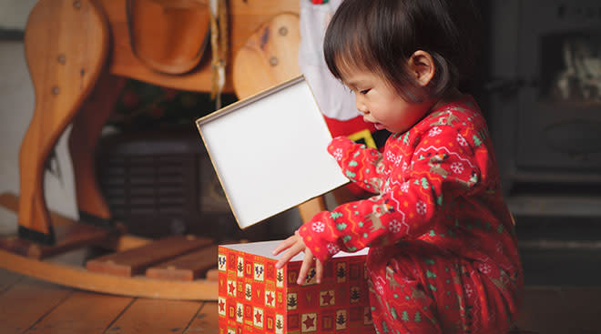 young child opening up holiday present