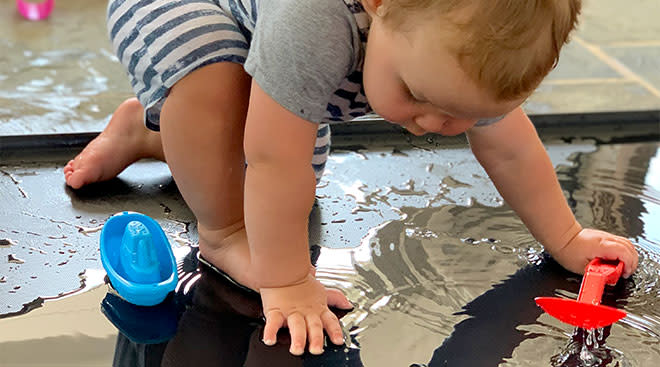Toddler doing sensory activity of stomping on water.