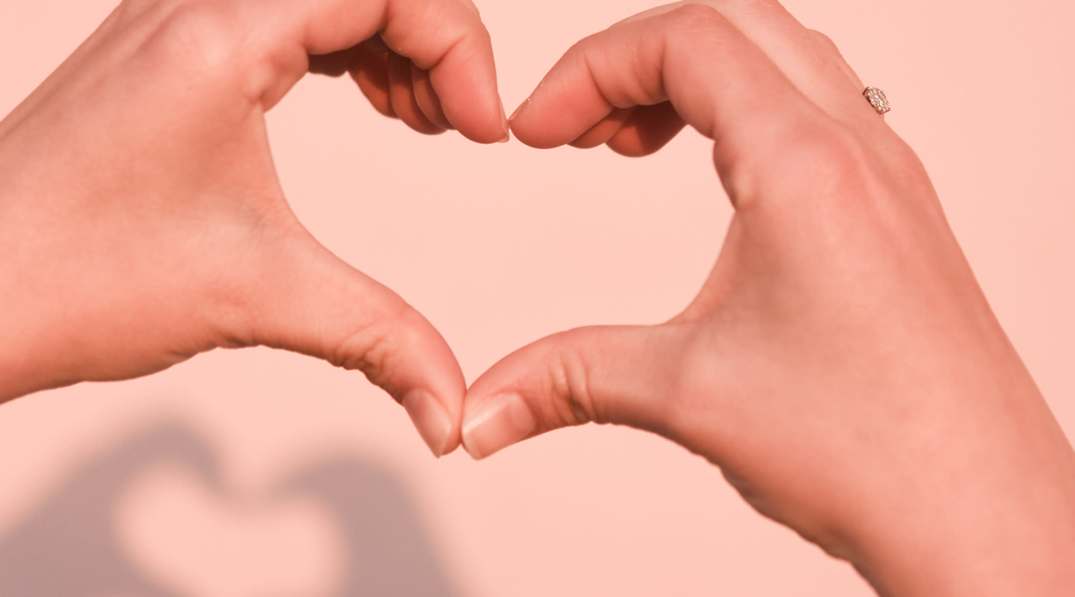 Two hands forming heart shape against pink background.