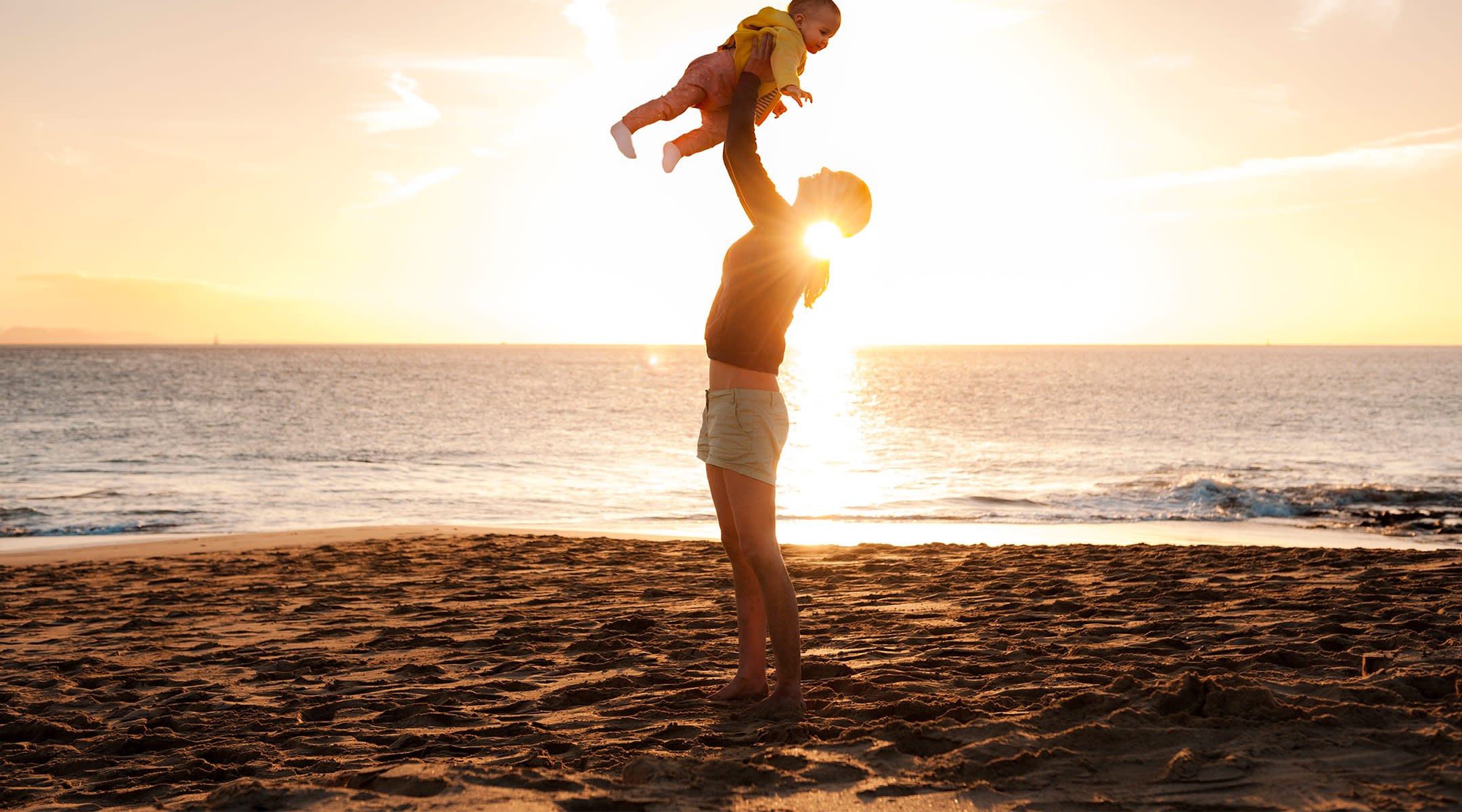 mom traveling with baby, lifting her into the air at the beach