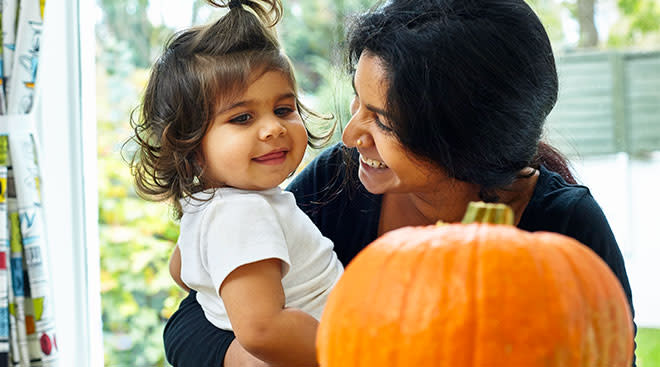 mom happily looking at her daughter about to carve a pumpkin for halloween