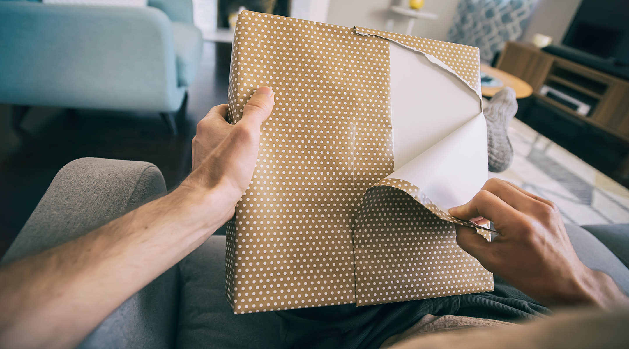 man opening gift at home