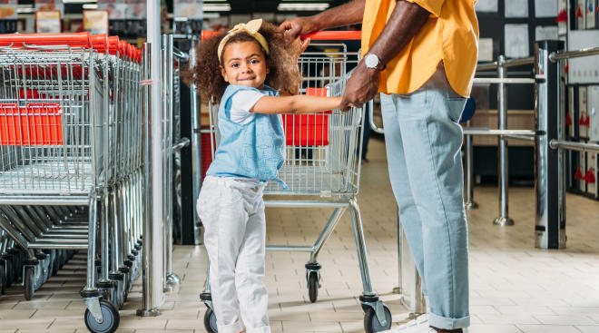 dad standing with his daughter by shopping carts outside a store