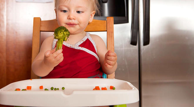 baby eating broccoli and maintaining variety in first foods