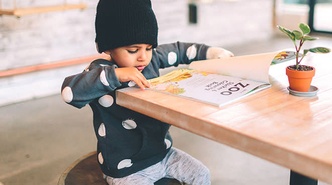 independent toddler reading a book at table