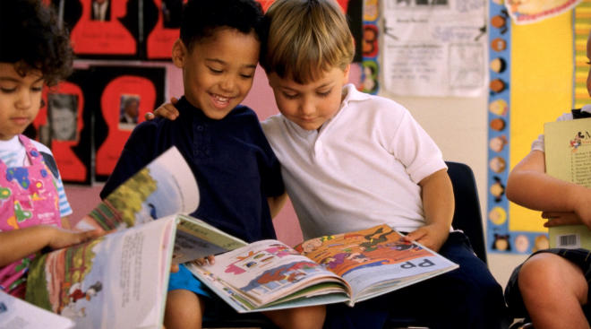 two little boys reading together in classroom