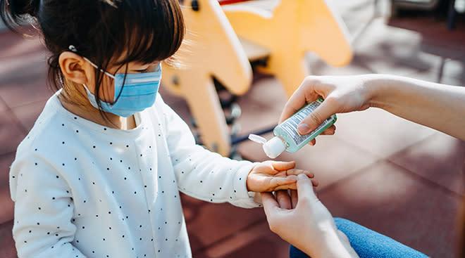 Mom applying hand sanitizer to child's hands