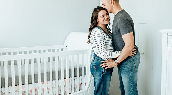 pregnant couple at home in their nursery