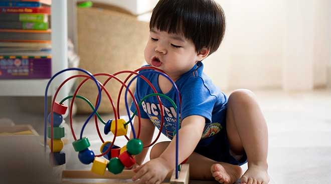 Toddler playing with wooden bead maze.