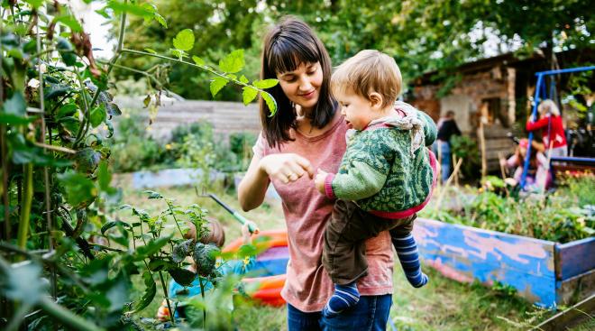 mom and toddler enjoying greenery in backyard