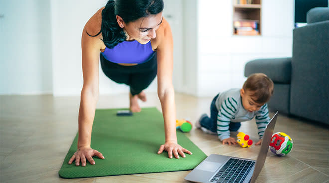 Mom exercises at home while her toddler who sits nearby refuses to nap.