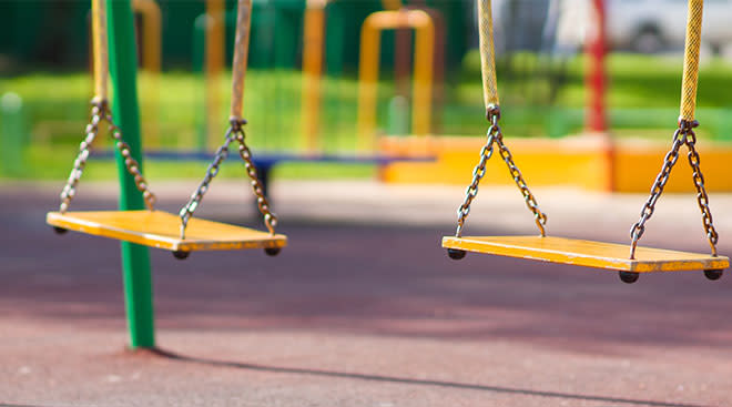 empty yellow swings in playground