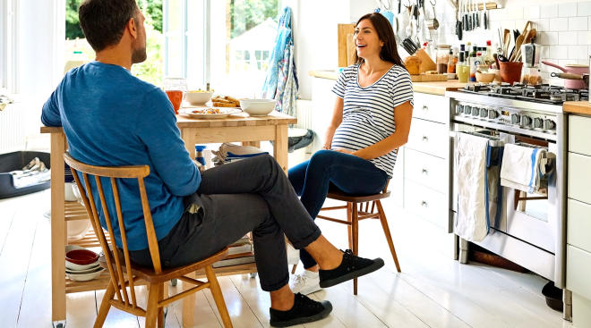 pregnant woman sitting in the kitchen with her partner
