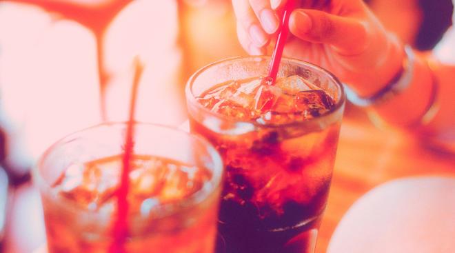 hand stirring straw in soda which has added sugar