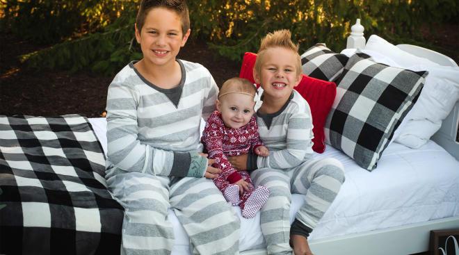 three siblings wearing matching holiday pajamas