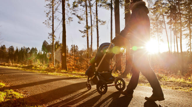 dad pushing lightweight stroller outside on path