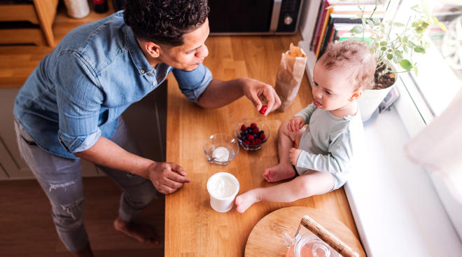 dad eating healthy food with his toddler in the kitchen